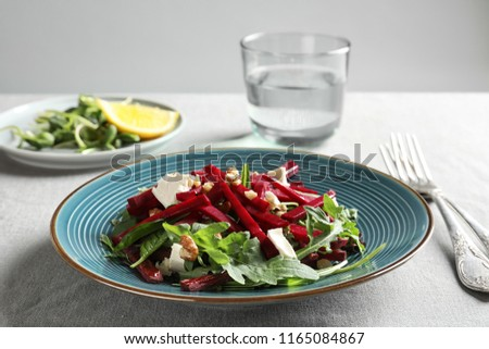 Plate with delicious beet salad served on table