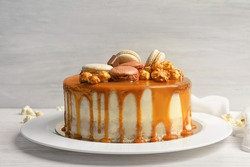 Plate with delicious caramel cake on table against light wall