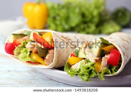Plate with delicious meat tortilla wraps on wooden table, closeup