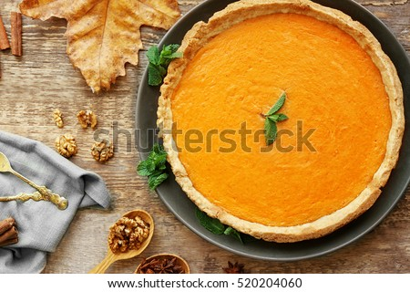 Plate with delicious pumpkin cake on wooden background