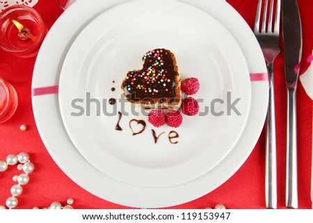 Plate with dessert in form of heart on celebratory table in honor of Valentine's Day close-up