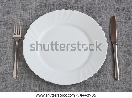 Plate with fork and knife on cotton background