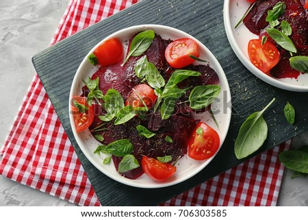 Plate with fresh beet salad on wooden board