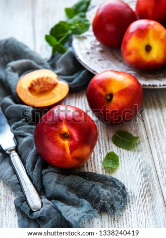 Plate with fresh nectarines on a white wooden table