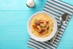 Plate with fresh tasty shrimp and grits on wooden table, top view