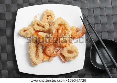 plate with fried mixed seafood with chopsticks on black tablecloth