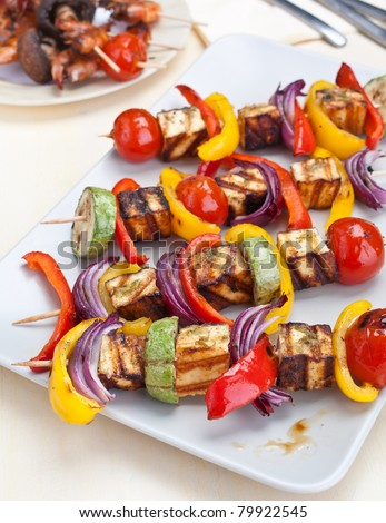 plate with halloumi and vegetables kebabs on a table