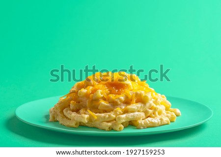 Plate with mac and cheese isolated on a green background. Macaroni with bechamel sauce and melted cheddar cheese on a green plate. Stock fotó ©