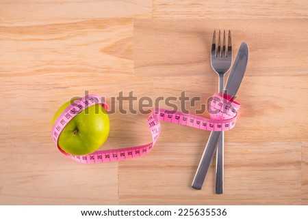 Plate with measure tape, knife and fork. Diet food on wooden table. apple and measuring tape on the floor scales isolated on white