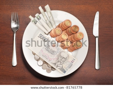 Plate with money instead of food symbolizing expensive food, consumerism or other food and money related concepts.