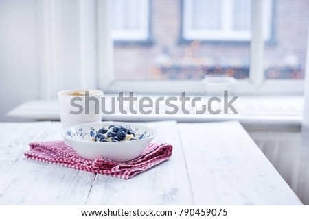 Plate with muesli and berries, coffee in a cup for breakfast. Napkin in a red cage on a white wooden table by the window. Free space for text.
