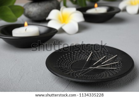 Plate with needles for acupuncture on table