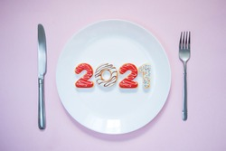 Plate with numbers 2021, knife and fork on pink background. Restaurant and food theme. Christmas. New Year . New Year's menu