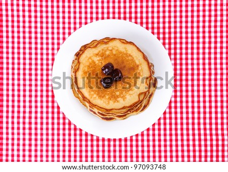 plate with pancakes on top of read and white checked tablecloth