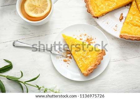 Plate with piece of tasty lemon pie and cup of tea on white wooden table