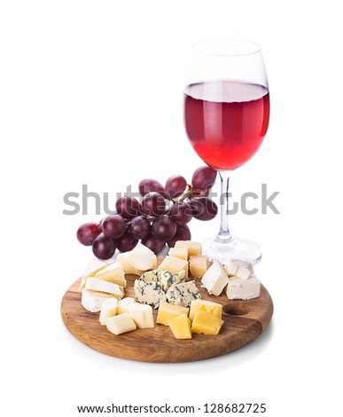 Plate with pieces of various types of cheese, grape and glass of wine, isolated on white