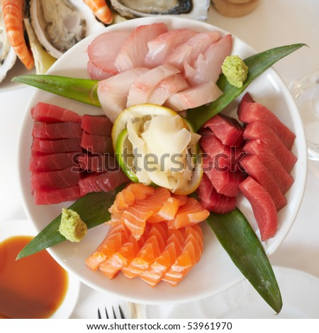 Plate with raw fish pieces, ginger and wasabi