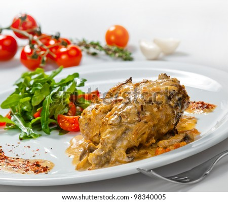 Plate with roasted rabbit  and vegetable garnish. - stock photo