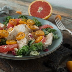 plate with salad with chicken breast fillet, grapefruit and kumquat close-up