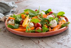plate with salad with mozzarella, arugula, pepper and tomatoes on the table