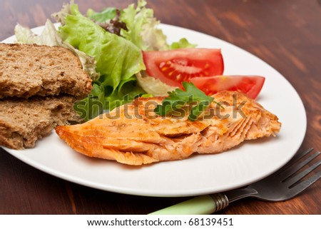 plate with salmon garnished with vegetables on a wooden table