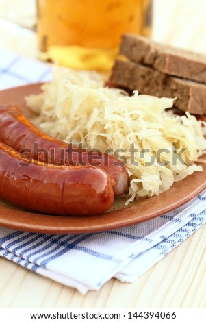 Plate with sausages and pickled cabbage, bread and beer.