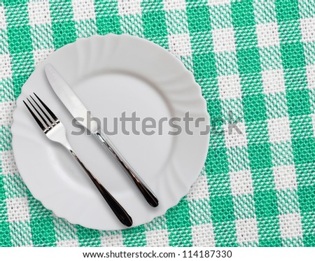 Plate with silverware on checkered green  background