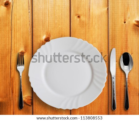 Plate with silverware on the wooden table