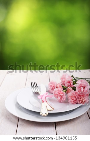 Plate with silverware on wooden table over green bokeh background