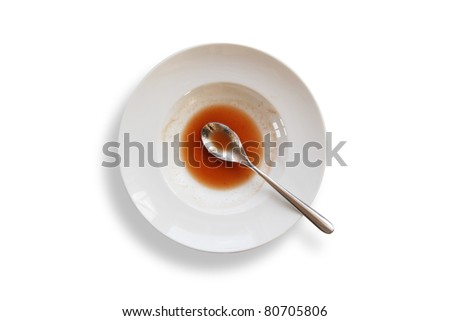 Plate with spoon and leftovers of tomato soup