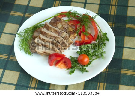 Plate with stew and vegetables on table covered in green plaid tablecloth
