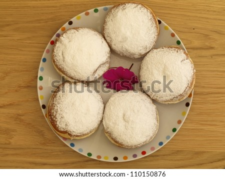 Plate with sweet donuts sprinkled with castor sugar