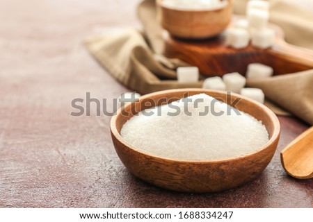 Plate with sweet sugar on color background