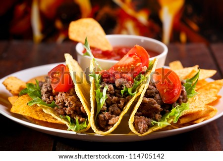 plate with taco, nachos chips and tomato dip - stock photo