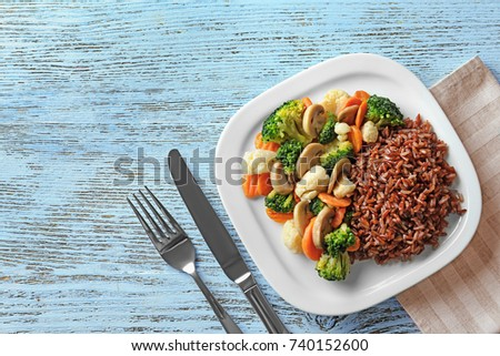 Plate with tasty brown rice and vegetables on wooden table #740152600