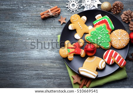 Plate with tasty Christmas cookies on wooden table #510669541