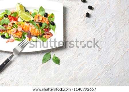 Plate with tasty fish and fresh salad on table #1140992657