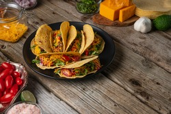 Plate with tasty mexican tacos on rustic wooden table with ingredients for cooking background. Concept of traditional meal. Side view.