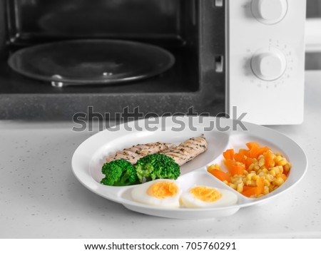 Plate with tasty organic food near microwave on table #705760291