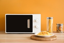 Plate with tasty pasta and microwave oven in kitchen