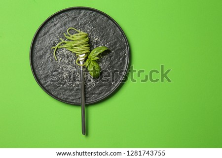 Plate with tasty pesto pasta on color background