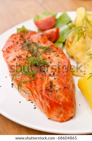 plate with tasty  salmon garnished with vegetables on a wooden table