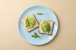 Plate with toasts with avocado, arugula and sesame on beige background, top view