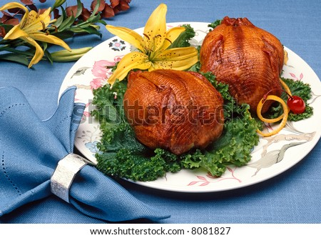 Plated Cornish Game hens with flower garnish