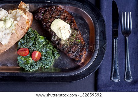 Plated New York Strip Steak With A Baked Potato