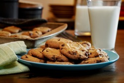 Plateful of chocolate chip cookies fresh and warm out of the oven with cold glass of milk