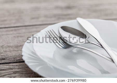 Plates and cutlery on wooden table #276939980