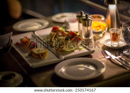 Plates and Dishes on the table in luxury restaurant. Sushi roll with salad. Romantic dinner with ambient light from candle.