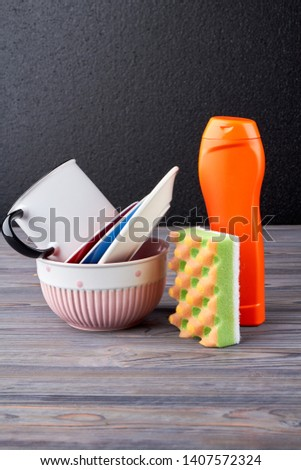 Plates, cup, detergent and sponge. Stack of clean plates, glass cup and cleaning product on wooden table. Household chores concept. #1407572324