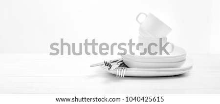 Plates, cups and silver cutlery on light white background
